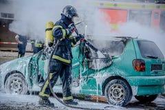 Mousse se renversante de sapeur-pompier sur une voiture brûlée images stock