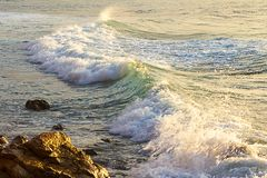 Moussera den skummande vågen som bryter på soluppgång arkivfoto