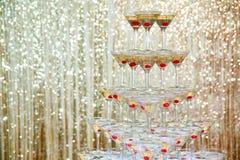 Mousserande champagnepyramid, torn av exponeringsglas på partiet framme av den guld- väggen Royaltyfria Bilder