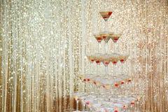 Mousserande champagnepyramid, torn av exponeringsglas på partiet framme av den guld- väggen Arkivbild
