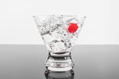 Mousserande dryck i ett martini exponeringsglas med en körsbär fotografering för bildbyråer