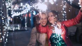 Mousserande fyrverkerier i nattstaden i händerna av flickor, som är lyckliga och att dansa och ha gyckel långsam rörelse lager videofilmer