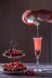 Mousserande rosa vin är hällt in exponeringsglas Ställning med jordgubbar Royaltyfri Fotografi