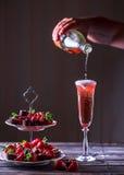 Mousserande rosa vin är hällt in exponeringsglas Ställning med jordgubbar Arkivfoto