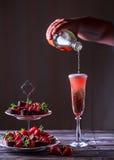 Mousserande rosa vin är hällt in exponeringsglas Ställning med jordgubbar Arkivbilder