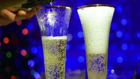 Mousserande vin hälls in i exponeringsglas I bakgrunden, bokehljusen och girlanderna av julgran Royaltyfri Bild