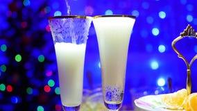 Mousserande vin hälls in i exponeringsglas I bakgrunden, bokehljusen och girlanderna av julgran Arkivfoto