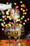 Mousserande vin hälls in i exponeringsglasen royaltyfria foton