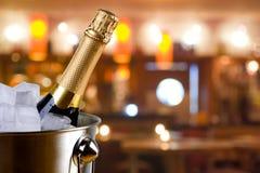 Mousserande vinflaska i ishink på suddig restaurangbakgrund Arkivbilder
