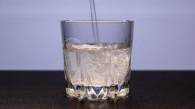 Mousserend mineraalwater wordt in een doorzichtig glas gegoten stock video