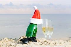 Mousserende wijn fles en het drinken glazen in zand op overzees strand royalty-vrije stock foto's
