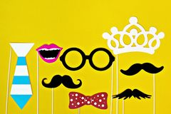 Moustache, δεσμός, γυαλιά, κόκκινο στόμα στα ξύλινα ραβδιά ενάντια δωρεές ενός στις φωτεινές κίτρινες υποβάθρου μήνα στοκ εικόνα