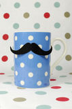 Moustache on a blue coffee mug Stock Photos