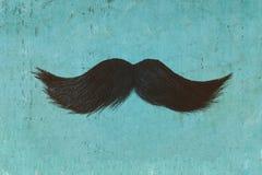 Moustache bouclée noire devant un fond bleu image stock
