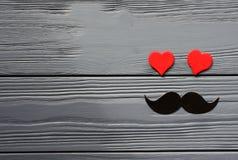 Moustache de papier et coeurs rouges sur le fond en bois gris Image libre de droits