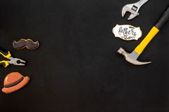 Moustache, hat, tools and copy for Happy Father Day party on black background top view copy space. Moustache, hat, set of tools and cookie with copy for Happy royalty free stock image