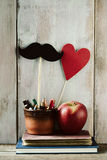 Moustache, heart, pencils, apple and books. Some pencils, a moustache and a red heart attached to sticks in an earthenware pot, a red apple and some books on a Stock Image