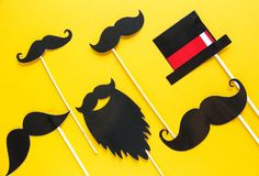 Moustache photo booth props on yellow background. Moustache cut outs. Prostate Cancer Awareness, Men health awareness concept. Flat lay, top view, copyspace royalty free stock photography