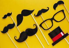 Moustache photo booth props on yellow background. Moustache cut outs. Prostate Cancer Awareness, Men health awareness concept. Flat lay, top view, copyspace royalty free stock image