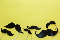 Moustache photo booth props on yellow background. Moustache cut outs. Prostate Cancer Awareness, Men health awareness concept. Flat lay, top view, copyspace stock image