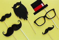 Moustache photo booth props on yellow background. Moustache cut outs. Prostate Cancer Awareness, Men health awareness concept. Flat lay, top view, copyspace stock photography