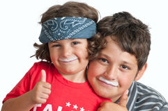 Moustached Siblings. Sister and brother having fun with thumbs up and milky white mustaches, isolated on a white background royalty free stock photo