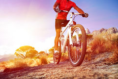Moutain bike man. Low angle view of cyclist riding mountain bike on rocky trail at sunrise Royalty Free Stock Images