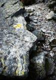 Moutain lapident le passage couvert de granit avec une flèche jaune Photos libres de droits