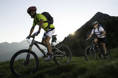 Moutainbiking by sunset - sunrise. Sunrise bike trail with two bikers Royalty Free Stock Photography