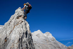 Moutaineering. Young woman with backpack climbing along sharp alpine ridge Stock Photo
