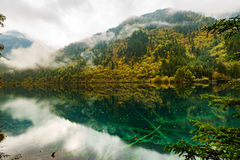 Moutains and Lakes in Jiuzhaigou Valley. Rivers and Lakes in Jiuzhaigou Valley with Cloudy sky.Fog floating around above mountains Stock Photo