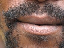 Mouth with beard. Close up of an african american male mouth surrounded by a beard Stock Image
