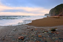 The mouth of the creek, which flows into the sea at sunset. Stock Photography