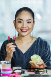 Mouth lipstick. Brunette woman applying make up in hand with mouth lipstick Royalty Free Stock Photo