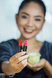 Mouth lipstick. Brunette woman applying make up in hand with mouth lipstick Stock Photos