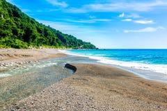 Mouth of the river to the sea on Playa Sana Rafael Beach, Barahona, Dominican Republic.  Royalty Free Stock Photos