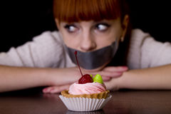 Mouth sealed with tape sad looking at cakes Stock Photo