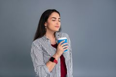 Pleasant dark-haired woman enjoying coffee scent. Mouth-watering aroma. Beautiful dark-haired woman holding a coffee cup and enjoying its scent while posing stock photo