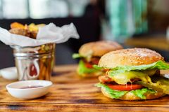 Delicious homemade burgers with a juicy veal cutlet on a wooden table stock photography