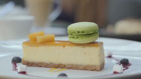 Beautifully served tasty cheesecake with mango and berries and green macaron in restaurant. Close up. Mouth watering served tasty fresh cheesecake with mango and stock footage