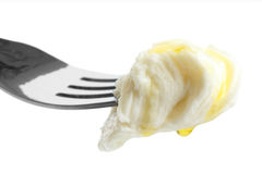 Mouthful of torn mozzarella dripping with oil on fork and isolat Stock Images
