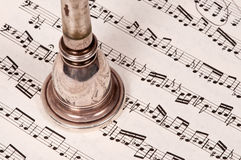 Mouthpiece Music. Well-worn, vintage mouthpiece atop sheet music Royalty Free Stock Image