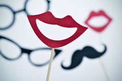 Mouths, eyeglasses and mustaches on sticks, vignetted royalty free stock photos