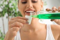 Mouthwash женщины лить от бутылки в крышку стоковое фото rf