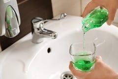 Mouthwash человека лить от бутылки в стекло стоковые изображения