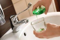 Mouthwash человека лить от бутылки в стекло стоковое фото