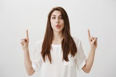 Mouthwatering advertisement. Portrait of funny attractive female student pointing upwards and showing tongue, being. Childish, fooling around over gray Royalty Free Stock Photography