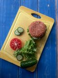 Mouthwatering burger and vegetables. Mouthwatering big beautiful burger with vegetables lying on the breadboard and wood royalty free stock image