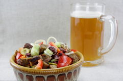 Mouthwatering salad and a glass of beer. Mouthwatering salad in an attractive bowl and a glass o home made beer. Grey texture background Royalty Free Stock Image