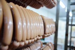 Mouthwatering smoked sausages on the background of a meat factory. Or butcher shop Royalty Free Stock Photo